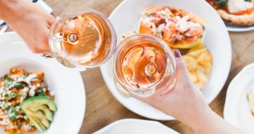 Two glasses of rose toasting over a spread of dishes