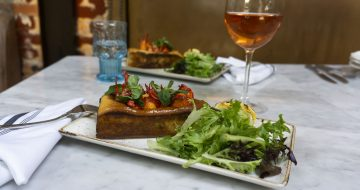 a dish of lobster roll, salad and glass of rose wine on a table