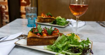 a dish of lobster roll, salad and glass of rose wine