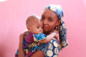 Mother and child, photographed in front of a vibrant wall outside of an Action Against Hunger Health Center in Cameroon.