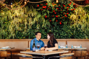 A couple at a dinner table with red wine at Herringbone Santa Monica in front of a lush wall of greenery