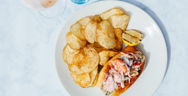 A glass of rose next to a lobster roll and potato chips